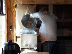 Ralph pours hot syrup, just off the evaporator, into the filter/canner
